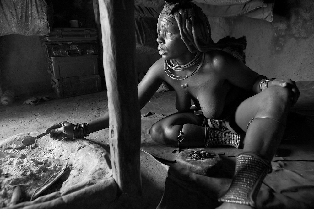 A Himba woman carries out teh ritual to paint her body with clay mixed with butter, and then smoke it with ashes in her little village near Opuwo, in Namibia, Africa.