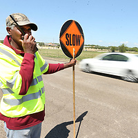 Phillip Adax, a flagman with Double G Road Construction, keeps the traffic moving on Jackson Street Extended during milling of the street Wednesday morning in Tupelo.