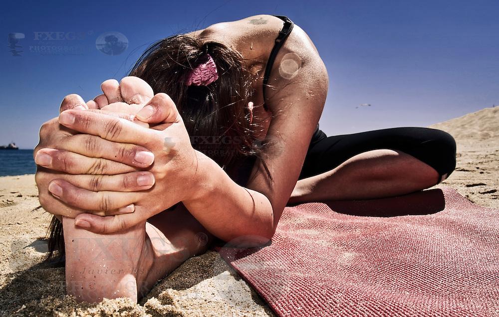 Mujer joven ejecutando una pose de yoga en la playa. Sesión en la playa de Valparaíso, Chile.