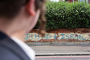 'Jihad 4 Israel'.  An Orthodox Jewish man walking past anti semitic graffiti on a wall in Leweston Place, Stamford Hill, London.