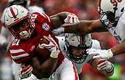 Nebraska Cornhuskers running back Mikale Wilbon (21) fights for yards as Northern Illinois Huskies defensive end Sutton Smith (15) and Northern Illinois Huskies defensive tackle William Lee (90) tackle him during a game on Saturday at Memorial Stadium in Lincoln. (Matt Gade / Republic)