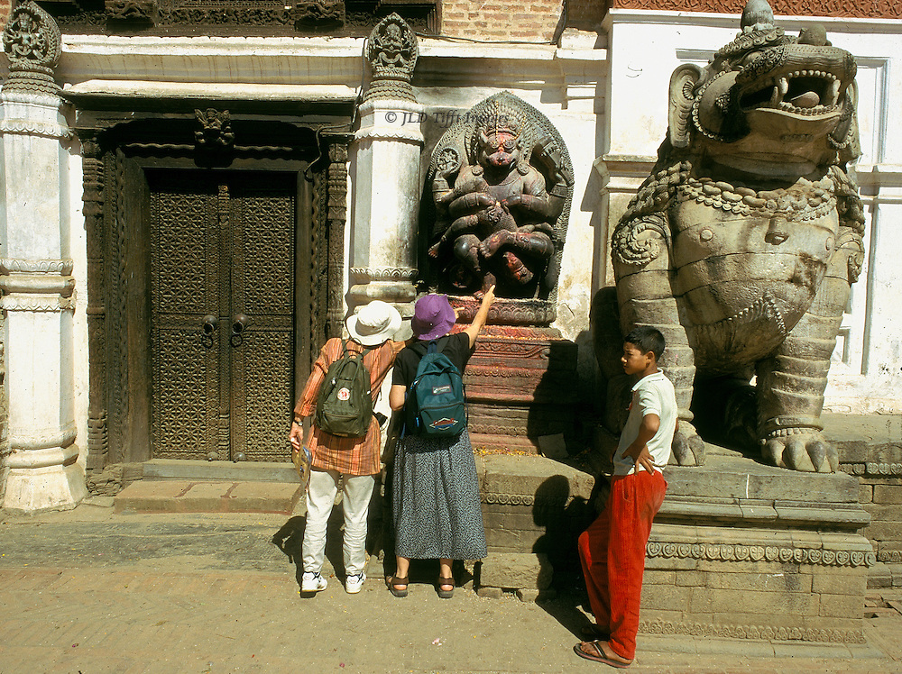 Outside the Lion Gate in Durbar Square, stone statue of a ferocious lion; behind it and to the left, a stone carving of Ugrachandi, the god Shiva's consort in her fearful manifestation.  Two women tourists examine the latter closely, one pointing to a feature; young Nepal man in red pants lounges against the lion statue as though waiting for them.