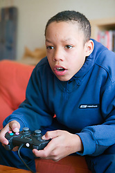 Boy concentrating on playing a computer game,