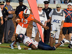 Virginia quarterback Brendan Lane (13) is tackled by Richmond quarterback Eric Ward (11) after returning a blocked field goal attempt by Richmond.  The Virginia Cavaliers defeated the #3 ranked (NCAA Division 1 Football Championship Subdivision) Richmond Spiders 16-0 in a NCAA football game held at Scott Stadium on the Grounds of the University of Virginia in Charlottesville, VA on September 6, 2008.