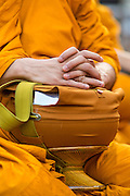 20 OCTOBER 2012 - BANGKOK, THAILAND: A monk cradles his alms bowl during an alms giving ceremony in Bangkok. More than 2,600 Buddhist Monks from across Bangkok and thousands of devout Thai Buddhists attended the mass alms giving ceremony in Benjasiri Park in Bangkok Saturday morning. The ceremony was to raise food and cash donations for Buddhist temples in Thailand's violence plagued southern provinces. Because of an ongoing long running insurgency by Muslim separatists many Buddhist monks in Pattani, Narathiwat and Yala, Thailand's three Muslim majority provinces, can't leave their temples without military escorts. Monks have been targeted by Muslim extremists because, in the view of the extremists, they represent the Thai state.        PHOTO BY JACK KURTZ