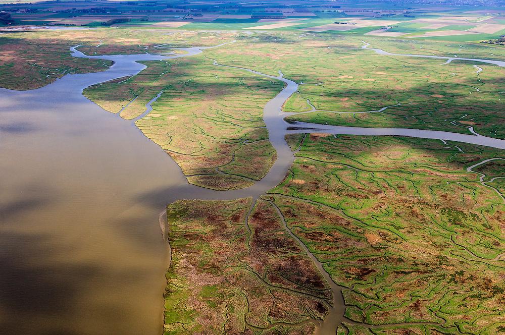 Nederland, Zeeland, Zeeuws-Vlaanderen, 09-05-2013; geulen, slikken en schorren in het Verdronken Land van Saeftinghe, getijdengebied in het oosten Zeeuws-Vlaanderen op de grens met Belgie en onderdeel van het estuarium van de Schelde. De voormalige polder is het grootste brakwatergebied van Europa en staat onder invloed van het getij. Het Verdronken Land is een natuurreservaat, in beheer bij het Zeeuws Landschap en belangrijk als broed-, overwinterings- en rustgebied voor vogels. Niet vrij toegankelijk. .The Drowned Land of Saeftinghe, tidal area in the east of Dutch Flanders on the border with Belgium. The former polder is the largest brackish water of Europe and because of the the tides, there are mud flats and gullies. The Drowned Land is a nature reserve, not freely accessible. It is managed by the Zeeuws Landscape and important as bird sanctuary, part of the Scheldt estuary..luchtfoto (toeslag op standard tarieven).aerial photo (additional fee required).copyright foto/photo Siebe Swart