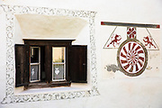 House in the Engadine Valley in the village of Guarda with old painted stone 17th Century window detail, Switzerland