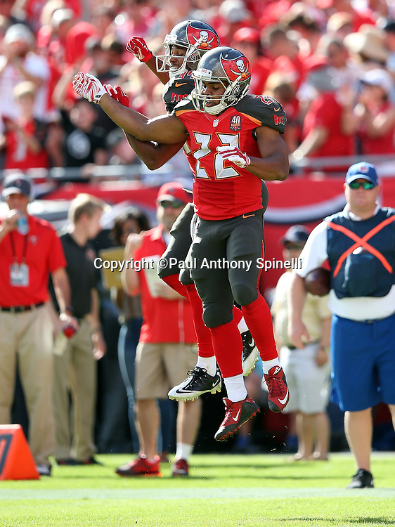 Tampa Bay Buccaneers running back Doug Martin (22) leaps and celebrates with Tampa Bay Buccaneers running back Charles Sims (34) after running for a second quarter touchdown that cuts the New Orleans Saints lead to 14-7 during the 2015 week 14 regular season NFL football game against the New Orleans Saints on Sunday, Dec. 13, 2015 in Tampa, Fla. The Saints won the game 24-17. (©Paul Anthony Spinelli)
