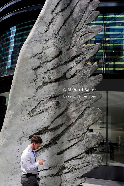 A financial industry buusinessman checks messages beneath the sculpture entitled City Wing on Threadneedle Street in the City of London, the capital's financial district (aka the Square Mile), on 11th July 2019, in London, England. City Wing is by the artist Christopher Le Brun. The ten-metre-tall bronze sculpture is by President of the Royal Academy of Arts, Christopher Le Brun, commissioned by Hammerson in 2009. It is called 'The City Wing' and has been cast by Morris Singer Art Founders, reputedly the oldest fine art foundry in the world.