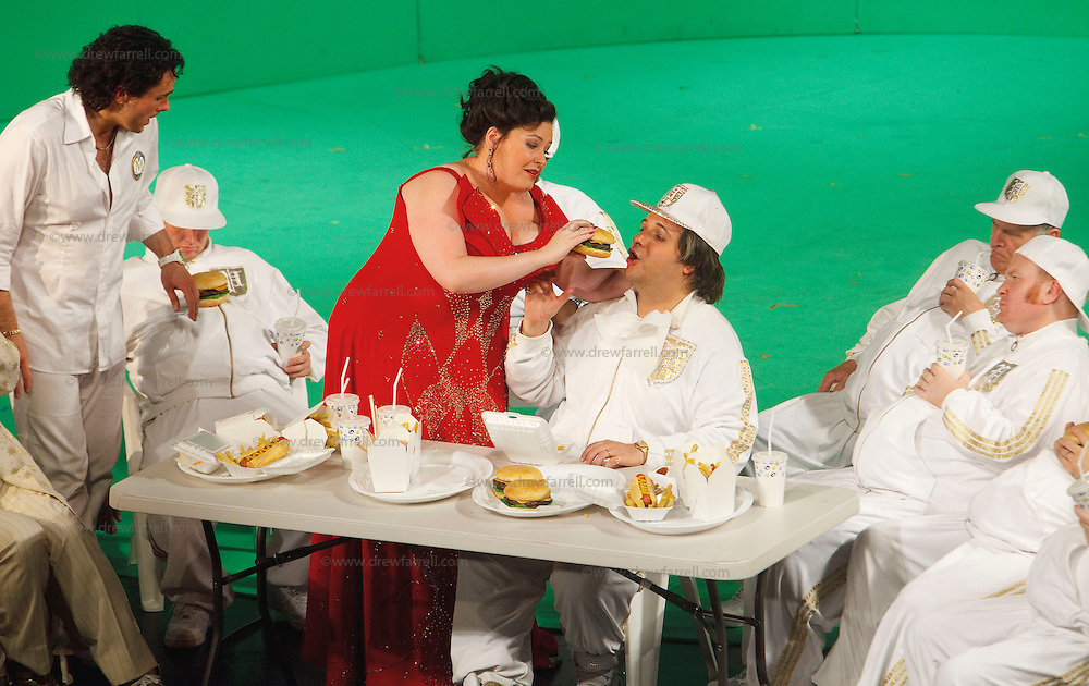 Picture shows : Tiziano Bracci as Mustafa being fed burgers by Karen Cargill as Isabella. Thomas Walker as Lindoro standing left..Picture  ©  Drew Farrell Tel : 07721 -735041..A new Scottish Opera production of  Rossini's 'The Italian Girl in Algiers' opens at The Theatre Royal Glasgow on Wednesday 21st October 2009..(Soap) opera as you've never seen it before..Tonight on Algiers.....Colin McColl's cheeky take on Rossini's comic opera is a riot of bunny girls, beach balls, and small screen heroes with big screen egos. Set in a TV studio during the filming of popular Latino soap, Algiers, the show pits Rossini's typically playful and lyrical music against the shoreline shenanigans of cast and crew. You'd think the scandal would be confined to the outrageous storylines, but there's as much action off set as there is on.... .Italian bass Tiziano Bracci makes his UK debut in the role of Mustafa. Scottish mezzo-soprano Karen Cargill, who the Guardian called a 'bright star' for her performance as Rosina in Scottish Opera's 2007 production of The Barber of Seville, sings Isabella. .Cast .Mustafa...Tiziano Bracci.Isabella..Karen Cargill.Lindoro...Thomas Walker.Elvira...Mary O'Sullivan.Zulma...Julia Riley.Haly...Paul Carey Jones.Taddeo...Adrian Powter. .Conductors.Wyn Davies.Derek Clarke (Nov 14). .Director by Colin McColl.Set and Lighting Designer by Tony Rabbit.Costume Designer by Nic Smillie..New co-production with New Zealand Opera.Production supported by.The Scottish Opera Syndicate.Sung in Italian with English supertitles..Performances.Theatre Royal, Glasgow - October 21, 25,29,31..Eden Court, Inverness - November 7. .His Majesty's Theatre, Aberdeen  - November 14..Festival Theatre,Edinburgh - November 21, 25, 27 ...Note to Editors:  This image is free to be used editorially in the promotion of Scottish Opera. Without prejudice ALL other licences without prior consent will be deemed a breach of copyright under the 1988. Copyright Design and Patents Act  and will be sub