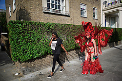 © Licensed to London News Pictures. 29/08/2016. London, UK. A carnival goer in costume makes her way to day two of the Notting Hill carnival, the second largest street festival in the world after the Rio Carnival in Brazil, attracting over 1 million people to the streets of West London.  Photo credit: Ben Cawthra/LNP