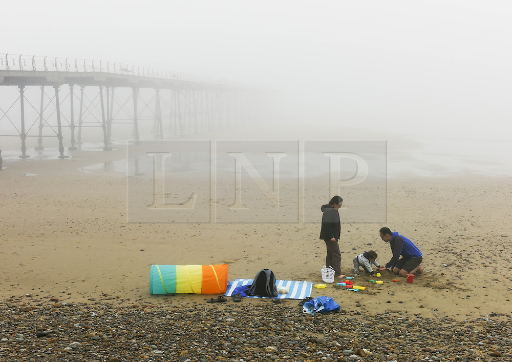 © Licensed to London News Pictures. <br /> 08/05/2016. <br /> Saltburn by the Sea, UK.  <br /> <br /> A family sit on the sand as heavy fog shrouds the coastline at Saltburn by the Sea in North Yorkshire as much of the country enjoys the hottest temperatures of the year so far.<br /> <br /> Photo credit: Ian Forsyth/LNP