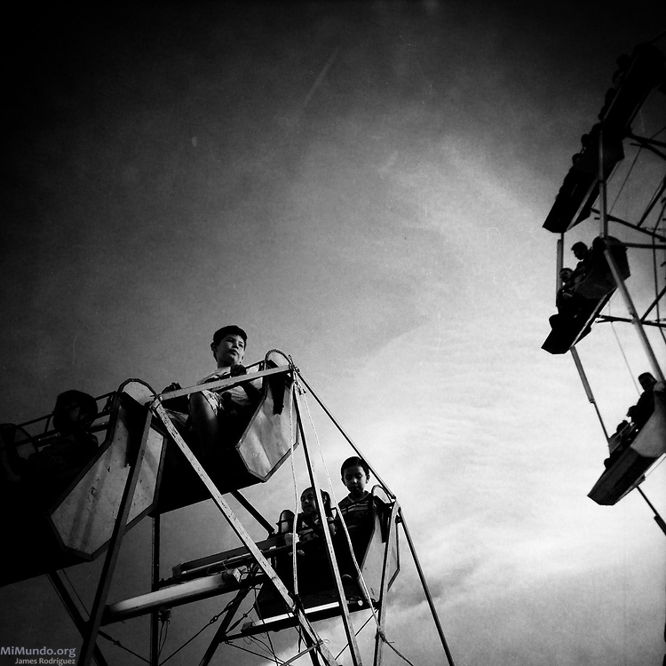 Niños observant desde una Rueda de Chicago durante la feria annual en Antigua, Guatemala. / Children ride a ferris wheel during the annual fair in Antigua, Guatemala. / Photo by James Rodríguez @mimundo_org #everydayguatemala #dailylife #Guatemala #everydaylatinamerica #fair #feria