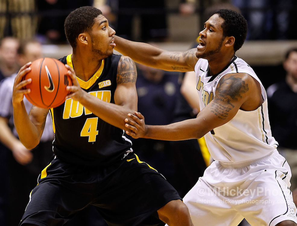 WEST LAFAYETTE, IN - JANUARY 27: Roy Devyn Marble #4 of the Iowa Hawkeyes holds the ball as Terone Johnson #0 of the Purdue Boilermakers defends at Mackey Arena on January 27, 2013 in West Lafayette, Indiana. Purdue defeated Iowa 65-62 in overtime. (Photo by Michael Hickey/Getty Images) *** Local Caption *** Roy Devyn Marble; Terone Johnson