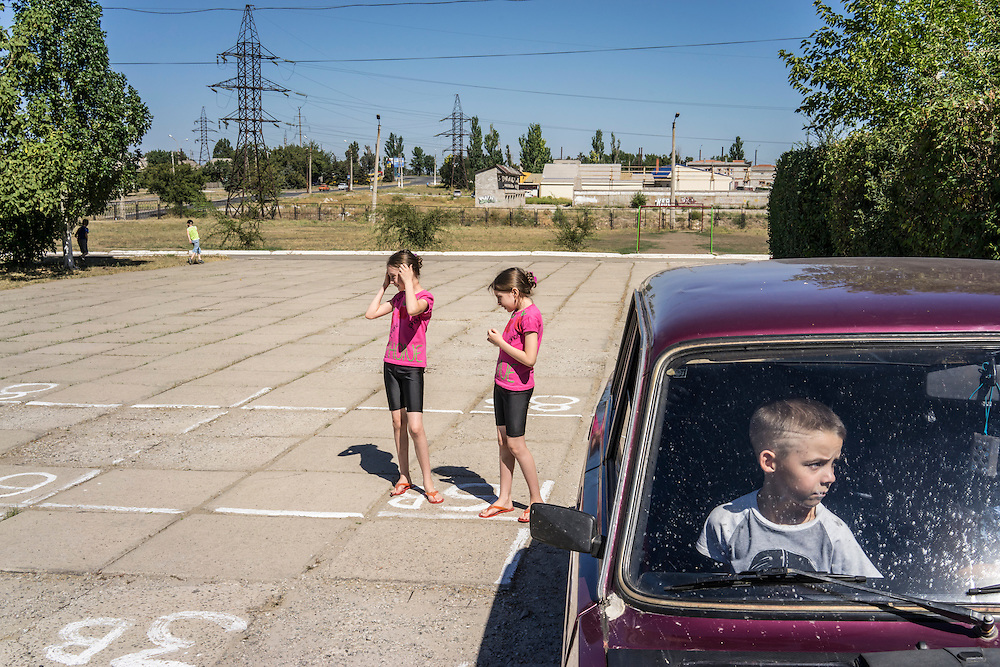 MARIUPOL, UKRAINE - AUGUST 31, 2015: Girls prepare to rehearse a dance production which they will perform on the first day of school at School 68 in Mariupol, Ukraine. A recent decrease in fighting has been credited to a desire to not interfere with the start of a new school year, planned for September 1. CREDIT: Brendan Hoffman for The New York Times