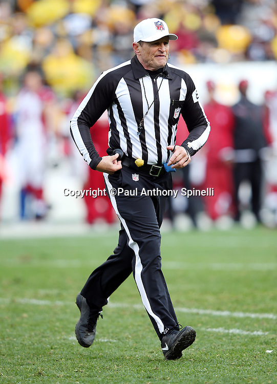 Referee Ed Hochuli (85) runs cross field during the Pittsburgh Steelers 2015 NFL week 6 regular season football game against the Arizona Cardinals on Sunday, Oct. 18, 2015 in Pittsburgh. The Steelers won the game 25-13. (©Paul Anthony Spinelli)