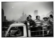 Road workers ride in the back of a truck while Shenzhen rises through the haze of a thick smog, Shenzhen, China.