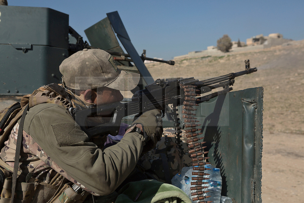 Licensed to London News Pictures. 20/02/2017. Albu Saif, Iraq. An Iraqi Emergency Response Soldier uses a machine gun to cover comrades assaulting the village of Albu Saif during the offensive to retake western Mosul from Islamic State militants.<br /> <br /> The settlement of Albu Saif is located on high ground overlooking Mosul Airport and as such is a strategic point that needs to be taken as part of the operation to retake the western side of Mosul. Photo credit: Matt Cetti-Roberts/LNP
