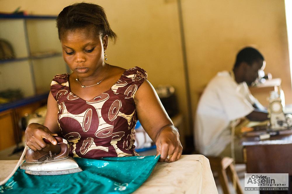 A woman irons clothes made at the Village Artisanal de Ouagadougou, a cooperative that employs dozens of artisans who work in different mediums, in Ouagadougou, Burkina Faso, on Monday November 3, 2008..