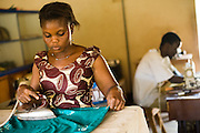A woman irons clothes made at the Village Artisanal de Ouagadougou, a cooperative that employs dozens of artisans who work in different mediums, in Ouagadougou, Burkina Faso, on Monday November 3, 2008..