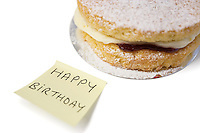Delicious cake slice with 'happy birthday' notepaper