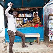 Afi Kanfji, sœur de  Khadija, devant son petit commerce avec un ami. Sa boutique, Kandji Cosmétique, a ouvert grâce à un prêt de la tontine