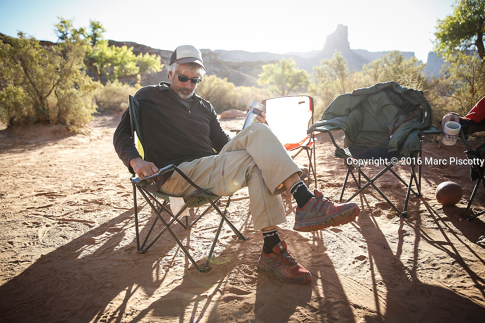 SHOT 10/15/16 9:08:01 AM - Paul Hobson of Steamboat Springs, Co. licking his wounds after a long night around the campfire during a White Rim mountain biking trip in Canyonlands National Park just outside of Moab, Utah. The White Rim Road is a 71.2-mile-long unpaved four-wheel drive road that traverses the top of the White Rim Sandstone formation below the Island in the Sky mesa of Canyonlands National Park in southern Utah in the United States. The road was constructed in the 1950s by the Atomic Energy Commission to provide access for individual prospectors intent on mining uranium deposits for use in nuclear weapons production during the Cold War. Four-wheel drive vehicles and mountain bikes are the most common modes of transport though horseback riding and hiking are also permitted.<br /> (Photo by Marc Piscotty / &copy; 2016)