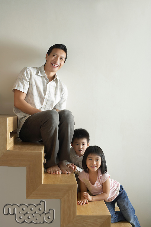Father Sitting with Children on wooden Staircase
