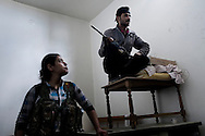 "SYRIA, ALEPPO : Engizek (R) the Kurdish woman leader of the ""Popular Protection Units"" (YPG) stands near by a comrade fighter inside a building in the majority-Kurdish Sheikh Maqsud district of the northern Syrian city of Aleppo, on April 16, 2013. ALESSIO ROMENZI"