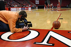 31 December 2006: Local TV videographer lines up an artsy shot with the basketball as the primary subject. The Bulldogs of Drake University dropped a conference match-up to the Redbirds 64-50 at Redbird Arena in Normal Illinois on the campus of Illinois State University.<br />