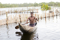 Man in a dugout canoe at a fishing village. People and places fine art photography prints. Exotic places wall art for sale.