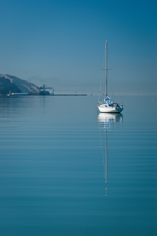 A yacht is moored in calm waters off Governors Bay, New Zealand, with the port of Lyttelton in the distance