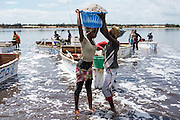 Women help each other to carry a salt bucket at the Lac Rose near Dakar, Senegal, on Tuesday, July 26, 2016. Photo by Xaume Olleros