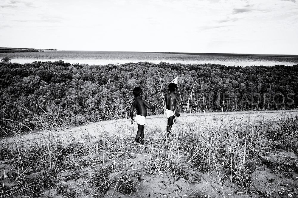 Meah (3 yr) and Marjorie (5 yr) playing on 'the Hill' which are the sand dunes behind their family home in Kennedy Hill. Free as little birds they run and play in the sand dunes, unaware of the problems their Community is dealing with. This is such a beautiful place, the sand is white, the water is turquoise, the sky is blue and the view is even more spectacular. This is a pristine location. Broome, Western Australia. ©Ingetje Tadros/Diimex