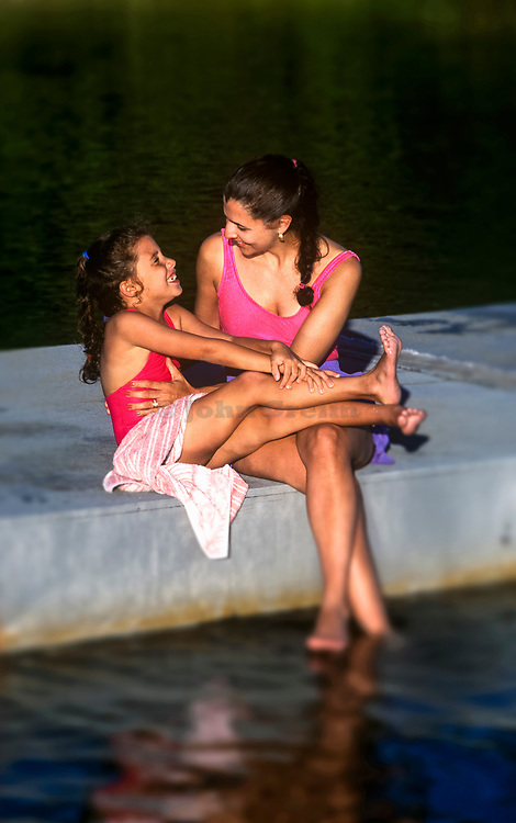 Young girl and mother bond on the dock of a lake, Cape Cod,