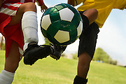 Two little league players (7-9 years) kicking ball mid air, mid section, close up