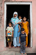 Nafeesa, 27, poses for a portrait with her 4 children aged 10, 7, 4, and 1.5 years, in her house compound in a slum in Tonk, Rajasthan, India, on 19th June 2012. Nafeesa's health deteriorated from bad birth spacing and over-working. While her husband works far from home, she rolls bidis (indian cigarettes) to make an income and support the family. She single-handedly runs the household and this has taken a toll on her health and financial insufficiencies has affected her children's health. Photo by Suzanne Lee for Save The Children UK