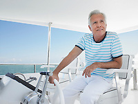 Middle-aged man sitting at helm of yacht