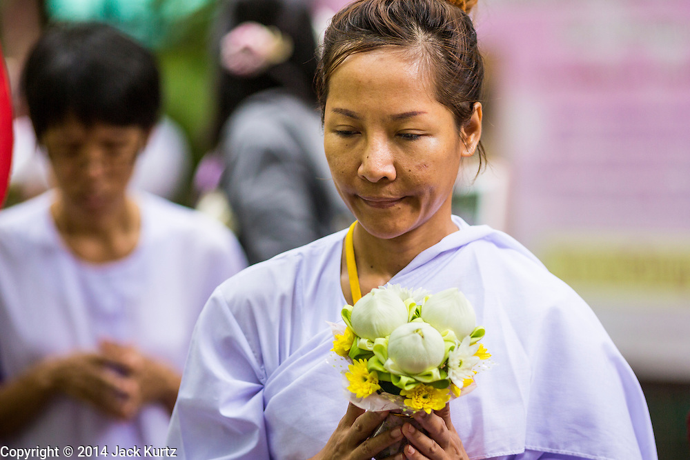 11 JULY 2014 - BANGKOK, THAILAND: A woman carries flowers around Wat Pathum Wanaram for Asalha Puja Day. Asalha Puja is the day the Lord Buddha preached his first sermon to followers after attaining enlightenment. The day is usually celebrated by merit making and listening to a monks' sermons. It is also day before the start of the Rains Retreat, the three month period when monks stay in their temple for intense mediation and spiritual renewal.    PHOTO BY JACK KURTZ