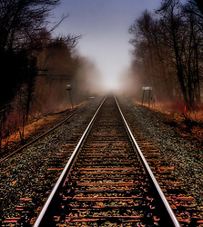 A rail line points an escape from an unsettling, firey foreground into a brighter, but obscure destiny. Hope it is not  train.