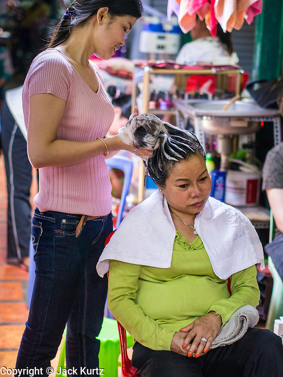 02 FEBRUARY 2013 - PHNOM PENH, CAMBODIA:   A woman has her hair done at a beauty parlor in a market in Phnom Penh, Cambodia.      PHOTO BY JACK KURTZ