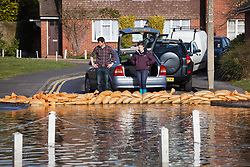 © Licensed to London News Pictures. 10/02/2014. Datchet, Berkshire, UK. People standing behind a line of sandbags which they have laid down to protect their properties from flooding. Flooding in Datchet today, 10th February 2014 after the River Thames burst its banks. Photo credit : Rob Arnold/LNP