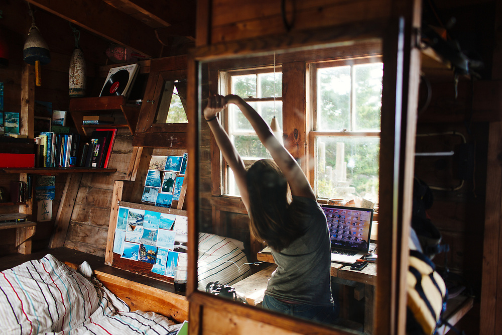 Womam Stretching and Using Laptop in Cabin, Vinalhaven, Maine.