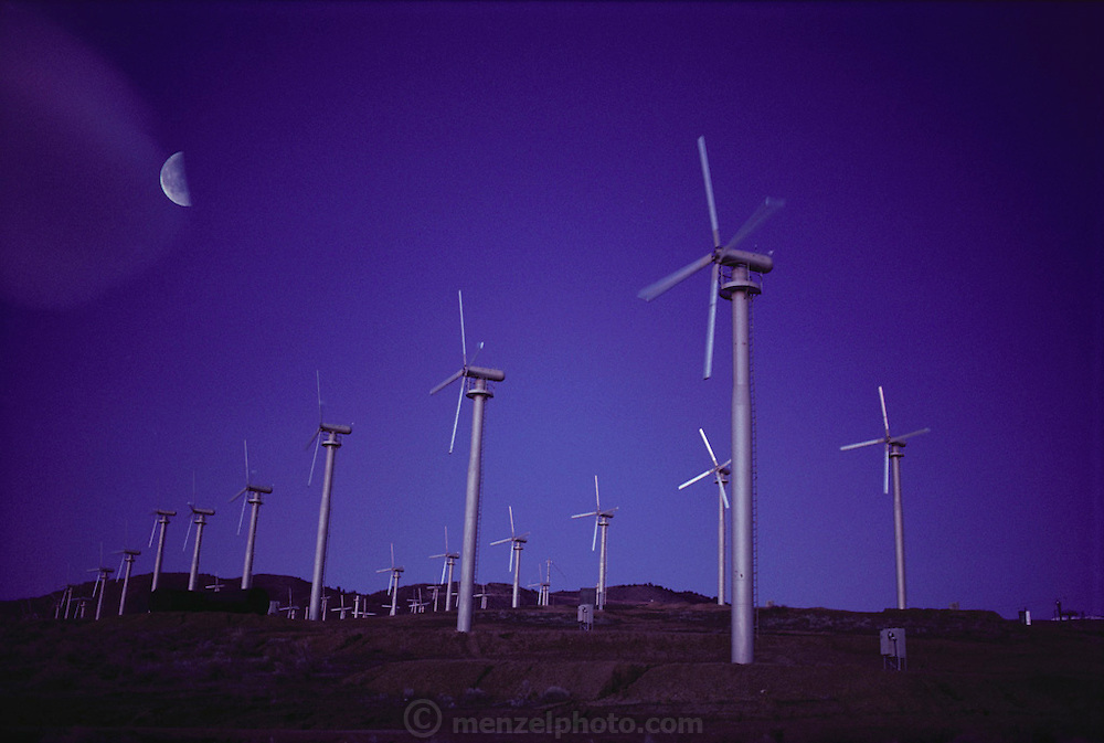 Wind farm producing electricity at Tehachapi Pass, southern California. Wind Turbines. View of a wind farm with several wind turbines each with 3 spinning rotor blades. Wind power is used to drive a turbine for the generation of electricity. The electrical energy produced from a turbine is proportional to the cube of the wind speed. Thus, a 10-meter per second wind will produce 8 times more energy than a 5 meter per second wind. Wind turbines vary in size from large generators with a 1-3 megawatt capacity to small machines producing only a few kilowatts. (1983).