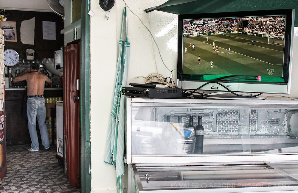a bare-chested man in one of many Lisbon bars. Outside a footbal match is broadcast on a open air TV.