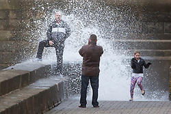 "© Licensed to London News Pictures. 09/11/2015. Bridlington, UK. FRAME 5 OF 9. A man poses for a photograph on the sea defences at the sea side town of Bridlington & gets caught out by a huge wave. The Yorkshire region was hit by severe gales this afternoon with winds up to 60mph. The Met Office warned West Yorkshire to expect gales and locally severe gales over high ground, with some ""very gusty"" winds to the east of high ground as well.<br /> Photo credit: Andrew McCaren/LNP"