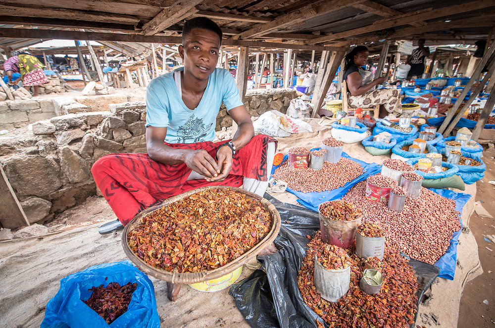 Man sits amongst produce in Ganta, Liberia