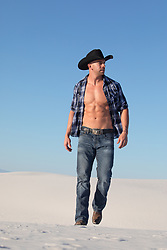 hot muscular cowboy with open shirt outdoors at sunset
