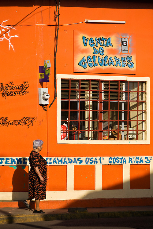 A woman walks past a brightly painted cyber cafe and cel phone rental store in Masaya. Masaya is located close to Granada, Nicaragua. It is a regional transportation hub and a famous market town where the products of the artisans of the surrounding towns are sold.