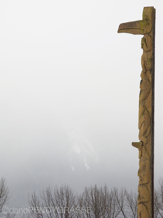 A totem Pole stands guard in front of barely visible mountains in Gitwinksihlkw, near Aiyansh, in British Columbia, Canada.